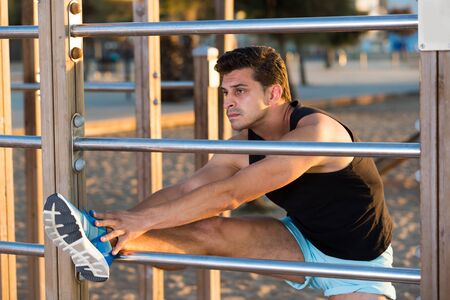 Strong man exercising in morning outdoors doing stretching workout on fitness station