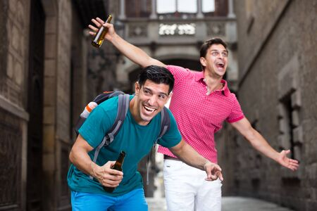 Two male fans are drinking beer after football match in Barcelona.