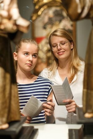 Portrait of woman visitor with daughter with guide book looking at exhibition in museum of ancient sculpture