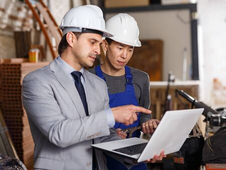 Male manager and professional builder using laptop with plan of building