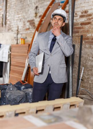 Male architect holding laptop and supervising process of building brick house Фото со стока