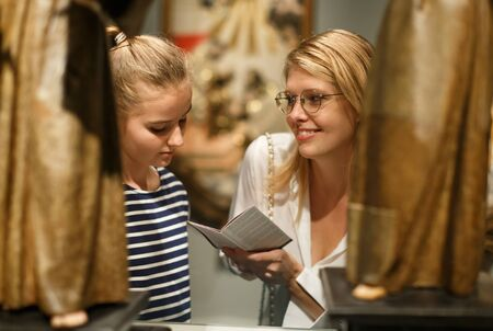 Portrait of woman visitor with daughter with guide book looking at exhibition in museum of ancient sculpture Imagens