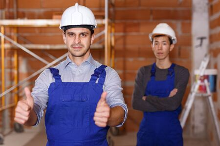 Two builders in work wear doing repair in brick private house