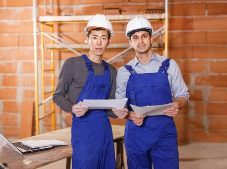 Portrait of two professional builders holding papers with plan of building Фото со стока