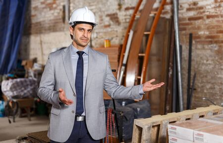 Portrait of friendly and welcoming man in suit and helmet at construction site