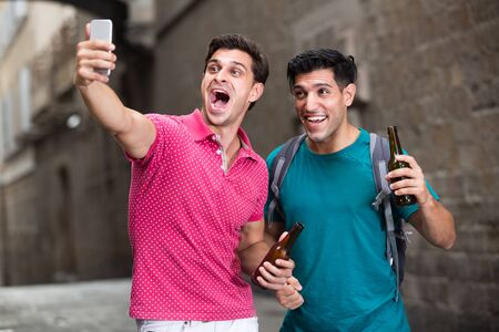 Two male fans are drinking beer and making selfie on smarphone after football match in Barcelona.