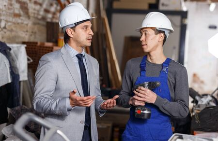 Portrait of male architect and professional worker talking at construction site 写真素材 - 130048940