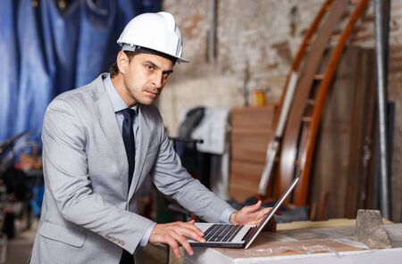 Confident male architect in suit and helmet controlling process of building using laptop