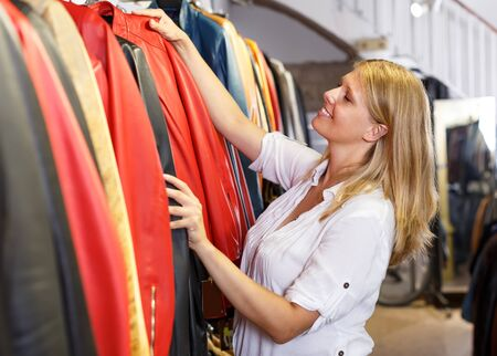 smiling young woman choosing stylish leather jacket in clothing store