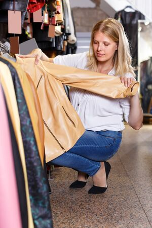 attentive young woman choosing stylish leather jacket in clothing store Stockfoto - 130048872