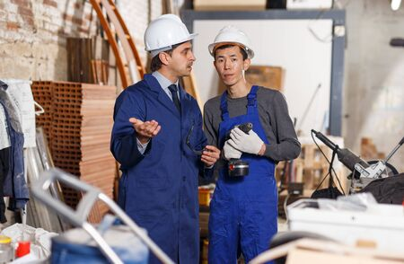 Male architect talking with worker in uniform about process of building brick house