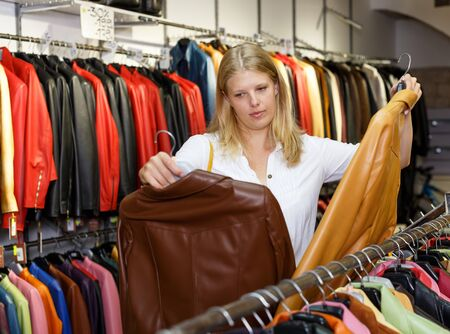 Attractive young blonde choosing leather jacket on racks in clothes store Stockfoto - 130047317