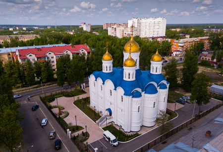 Aerial view of Cathedral of Icon of Our Lady of Jerusalem on background with modern cityscape of Russian town of Voskresensk