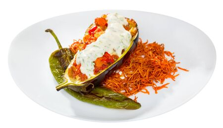 Tasty eggplant stuffed with baked vegetables in sauce served with carrot chips on plate. Isolated over white background