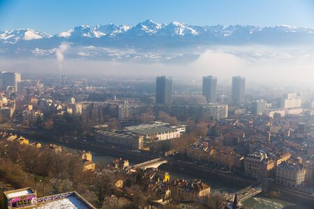 Aerial view of Grenoble against backdrop of snowy Alps in sunny day, France