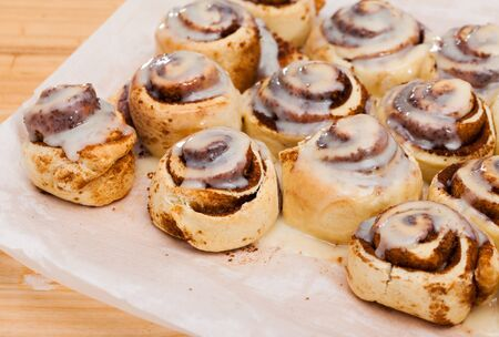 Appetizing rolled cinnamon buns in sugar and vanilla icing on white baking paper 스톡 콘텐츠