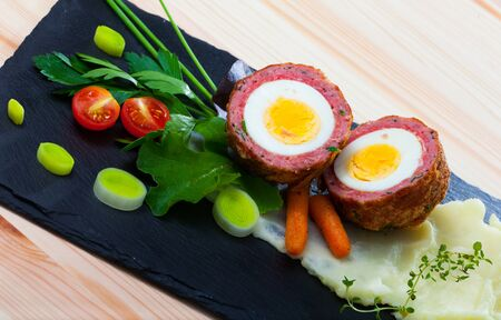 Dishes of traditional Scottish cuisine of scotch egg served with greens and potatoes at plate Imagens