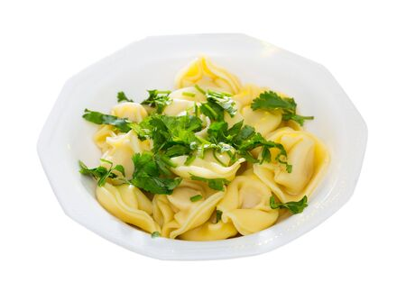 Plate of delicious freshly boiled ravioli with greens. Isolated over white background