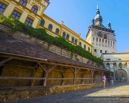 View of medieval clock tower from fortress square, famous tourist attraction in romanian town Sighisoara Imagens