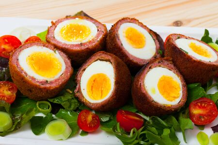 Tasty dish scotch eggs with tomatoes, greens and leek, traditional Scottish cuisine