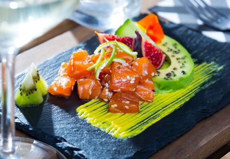 Fish tartare of raw tuna with slice of avocado and spicy mango sauce on black serving board