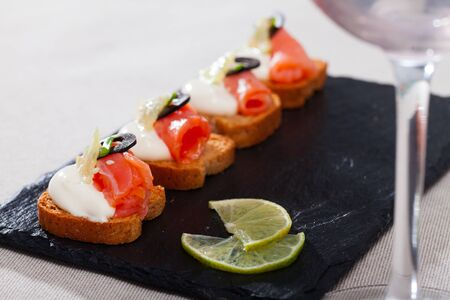 Close up image of canape with salmon and olives dressed with white sauce Stock fotó