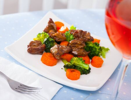 Roasted chicken hearts served with colorful garnish of green broccoli and orange carrots on white dish Stock fotó