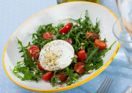 Appetizing salad with soft Burrata cheese, cherry tomatoes and greens Stock fotó