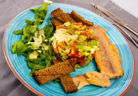 Image of tasty salad guacamole with arugula and tomatoes aerved with grilled trout fillet at plate Stockfoto - 130047954