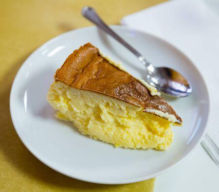 Zoet roomkaasdessert. Plak van Spaanse cheesecake Tarta de queso op witte plaat