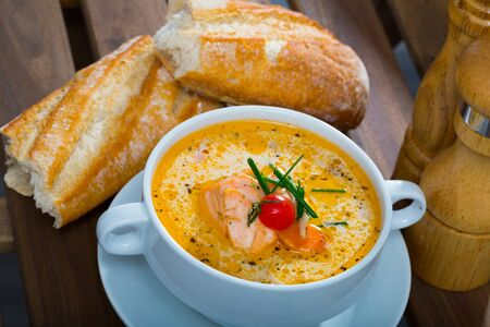 Delicious creamy salmon soup in white bowl with baguette - traditional dish of Norwegian cuisine