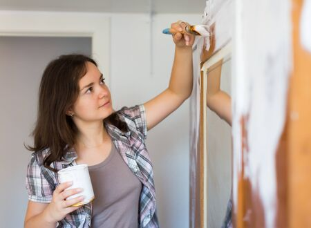 Young woman paints closet and makes repairs in the apartment 版權商用圖片