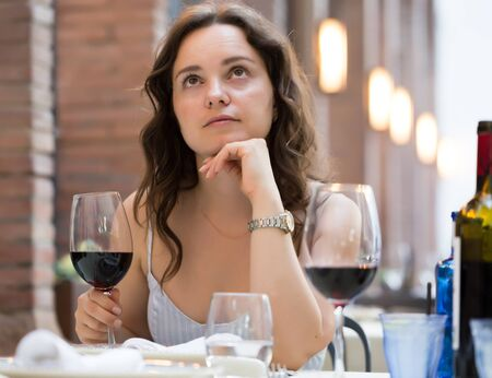 Young woman with glass of red wine sitting at outdoor restaurant Banco de Imagens