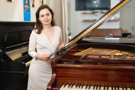 Pretty woman seller in piano music store