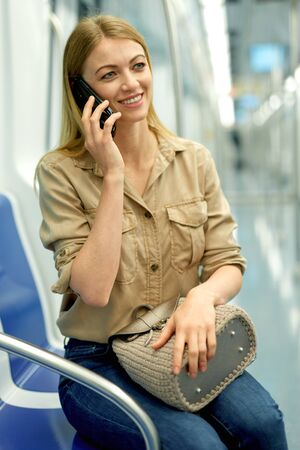 Nice girl speaks on the mobile phone in the subway train