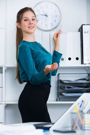 Young woman working in office standing near shelves with folders