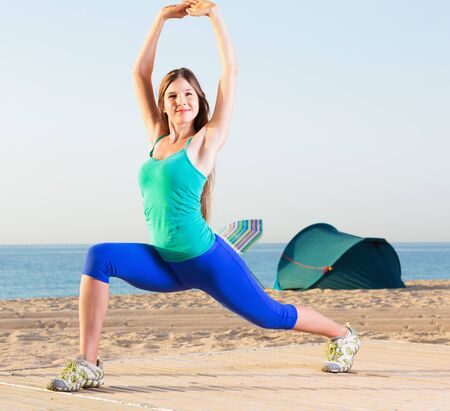 Portrait of glad beautiful positive sportswoman which is doing excercises on endurance on the beach near sea.