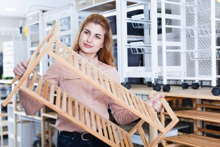 Positive girl looking for two-tier bamboo stackable shoe rack in shop