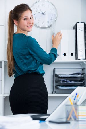 Smiling young business woman standing in half-turn at office interior
