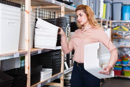 Modern female housewife choosing plastic tidy storage baskets in store