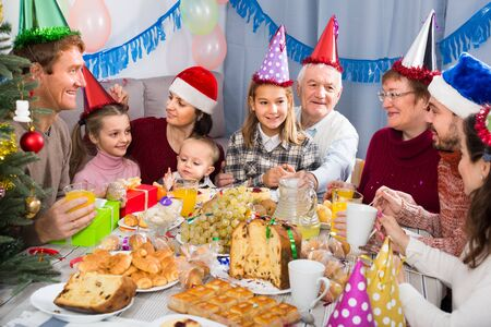 Family members having celebration of childrens birthday during dinner Фото со стока