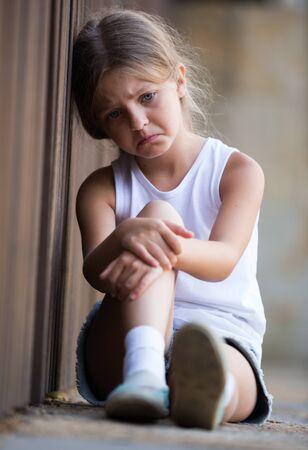 Mädchen im Grundschulalter, das draußen im Park depressiv schaut Standard-Bild