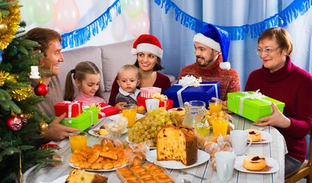 Large cheerful family exchanging gifts during Christmas dinner