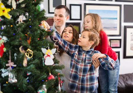 Young cheerful  family decorating Christmas tree at home Standard-Bild - 130143920