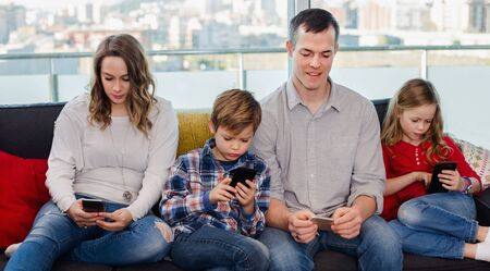Young happy smiling cheerful family playing with their smartphones together at home