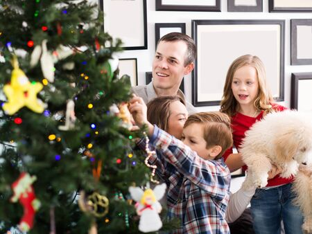 Happy family members decorates Christmas tree together at home Standard-Bild - 130143929