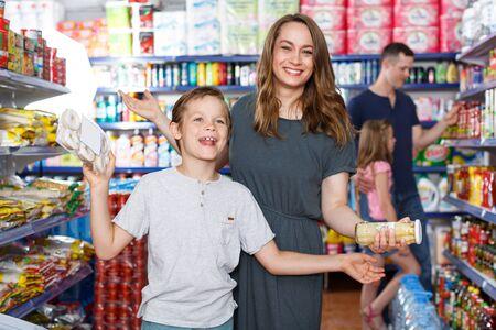 Mère et fils émotifs avec repas pour la maison, famille au supermarché