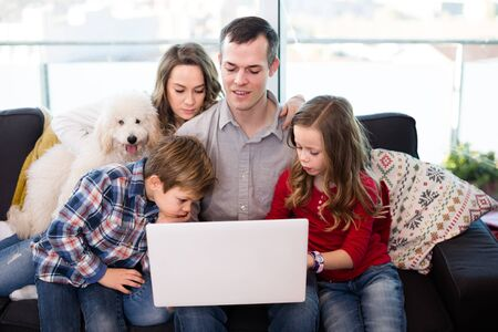 Young smiling family watching movie on laptop together at home on the couch