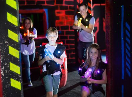 Cheerful little boy and girl with laser guns having fun with adults on dark lasertag arena