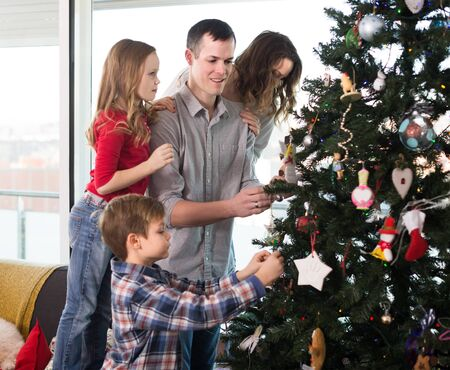 Parents with children preparing for Christmas together at home